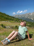 A smiling boy is sitting on slope in mountains Stock Images