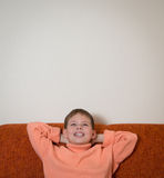 Smiling boy sitting on sofa and dreaming. Child looking up and relaxing at home. Copy-space. Royalty Free Stock Image