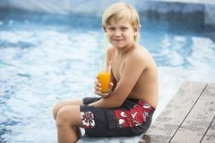 Boy drinking juice by pool royalty free stock image