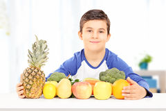 Smiling boy sitting at table full of fruits and vegetables indoo Royalty Free Stock Photography