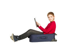 Smiling boy sitting in travel bag using tablet isolated on white Royalty Free Stock Photography