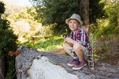 Smiling boy sitting on the tree trunk in the forest. Portrait of smiling boy sitting on the tree trunk in the forest Royalty Free Stock Photo