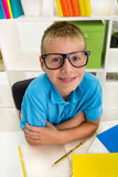 Smiling boy sitting in worktable Royalty Free Stock Images