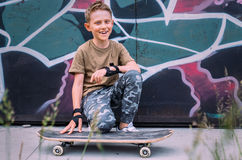 Smiling boy with skateboard sits near grafity painted wall Royalty Free Stock Images