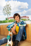 Smiling boy with skateboard sitting alone Stock Photography