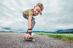 Smiling boy skates on skateboard Stock Photo