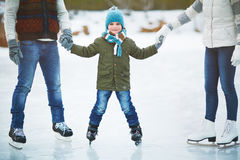 Smiling boy skating with parents Royalty Free Stock Photography