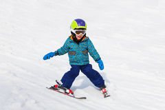 Smiling boy in ski mask learns skiing stock photography