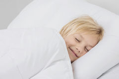 Smiling boy sleep in bed. Cheerful smiling blond boy sleep in white bed Royalty Free Stock Image