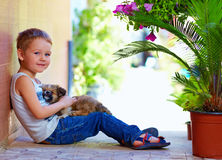Smiling boy with sleeping puppy in hands Stock Photo