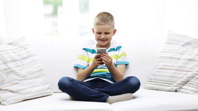 Smiling boy with smartphone at home Stock Images