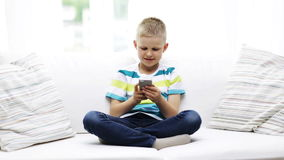 Smiling boy with smartphone at home Royalty Free Stock Photo