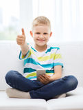 Smiling boy with smartphone showing thumbs up Royalty Free Stock Images