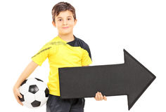 Smiling boy in sportswear holding a soccer ball and arrow pointi Stock Photo