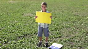 Smiling boy standing with empty blank banner