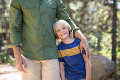 Smiling boy standing with father on sunny day in forest Royalty Free Stock Images