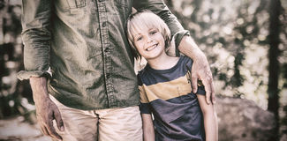 Smiling boy standing with father on sunny day in forest Royalty Free Stock Image