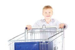 Smiling boy is standing near shoping basket Royalty Free Stock Photo