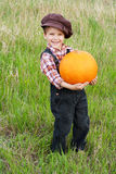 Smiling boy standing with pumpkin Royalty Free Stock Images