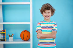Smiling boy standing beside some toys. In a room stock image