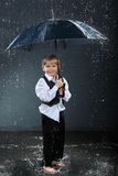 Smiling boy standing under umbrella in rain Stock Photos