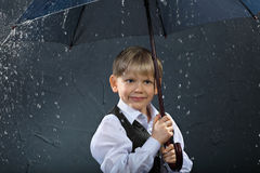 Smiling boy standing under umbrella in rain Stock Images