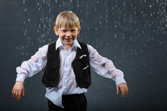 Smiling boy stands in rain stock photos