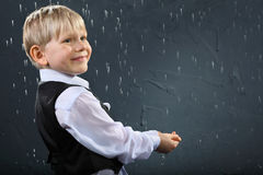 Smiling boy stands in rain and catches drops Stock Photo