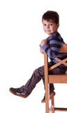 Smiling boy with striped t-shirt sitting on a  stool on white ba Stock Photo