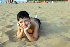 Smiling boy sunbathes on a beach. In a sunny day the boy lies on a beach on sand Royalty Free Stock Images