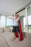 Smiling boy in super hero costume standing with arm outstretched on sofa bed at home Stock Image