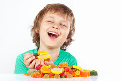 Smiling boy with sweets and jelly candies on white background Stock Photos