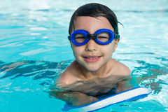 Smiling boy with swim goggles swimming in the pool Stock Image
