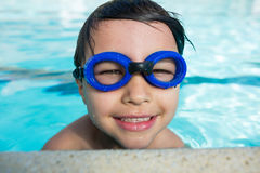 Smiling boy with swim goggles swimming in the pool Royalty Free Stock Images