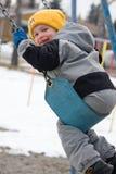 Smiling boy swinging stock image