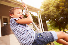Smiling boy swinging on a rope at a playground Royalty Free Stock Images