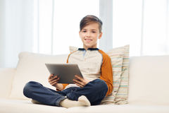 Smiling boy with tablet computer at home Royalty Free Stock Images