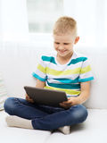 Smiling boy with tablet computer at home Stock Photos