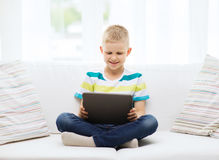 Smiling boy with tablet computer at home Stock Image
