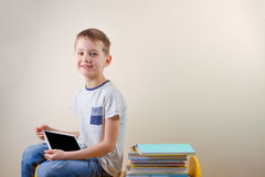 Smiling boy with tablet computer and stack of books near him. Happy child with tablet computer and stack of books near him Royalty Free Stock Images
