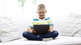 Smiling boy with tablet pc computer at home stock video footage