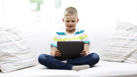 Smiling boy with tablet pc computer at home Stock Photography