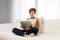 Smiling boy with tablet pc computer at home royalty free stock images