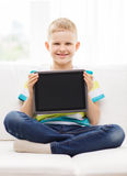 Smiling boy with tablet pc computer at home. Home, leisure, advertising and technology concept - smiling little boy with blank black tablet pc computer screen at royalty free stock photo