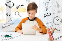 Smiling boy with tablet pc and notebook at home Stock Images