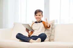 Smiling boy with tablet showing thumbs up at home Stock Photos