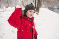 Smiling boy throwing snowball Royalty Free Stock Photography