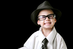 Smiling boy with tie. Cute boy with blue eyes wearing adult shirt with a tie and a hat, smiling,  isolated on a black background Royalty Free Stock Photo
