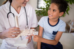 Smiling boy touching artificial bone held by female therapist. At hospital ward Royalty Free Stock Images