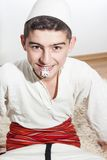 Smiling boy in traditional costume biting the eagle chest Stock Photo
